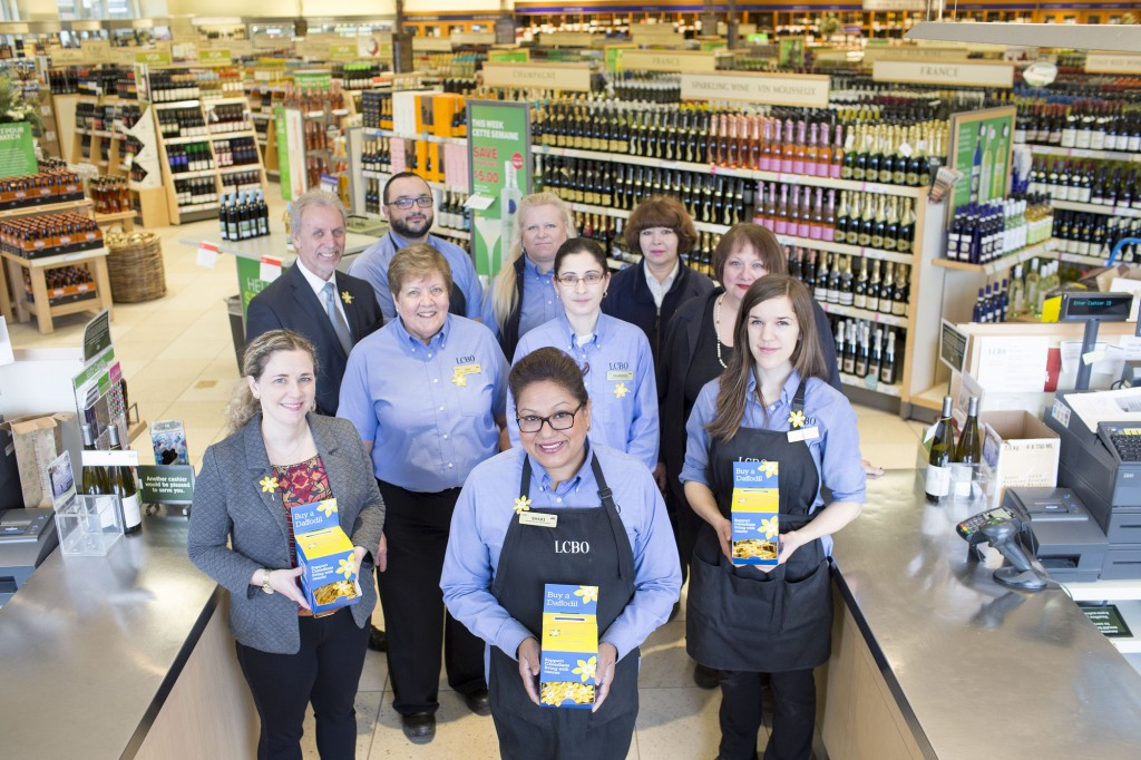 The team at the Dupont and Spadina LCBO store in Toronto join Susan Drodge (far left) of the Canadian Cancer Society to kick off Daffodil Month pin sales efforts at the LCBO'-s more than 650 stores across Ontario. (CNW Group/Canadian Cancer Society (Ontario Division))