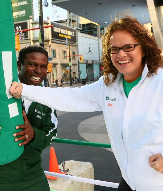Manulife Canada President and CEO Marianne Harrison punches a message at the Manulife Vitality Workout Computer with Coach Michael 'Pinball' Clemons in Toronto to launch Manulife Vitality, a new kind of life insurance that rewards healthy living. (CNW Group/Manulife Financial Corporation)