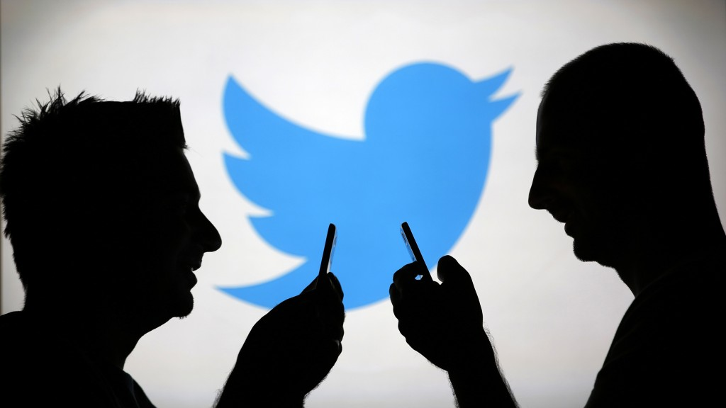 Men are silhouetted against a video screen with an Twitter logo as he poses with an Samsung S4 smartphone in this photo illustration taken in the central Bosnian town of Zenica, August 14, 2013. REUTERS/Dado Ruvic (BOSNIA AND HERZEGOVINA - Tags: BUSINESS TELECOMS)
